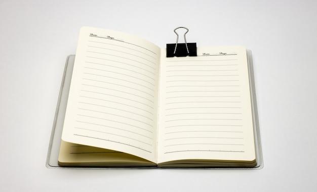 添付の黒いバインダークリップで白い背景のノートブックを開く