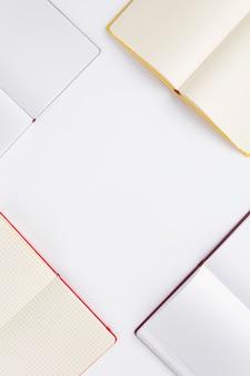 Откройте блокнот или книгу с пустыми страницами на белом фоне, вид сверху