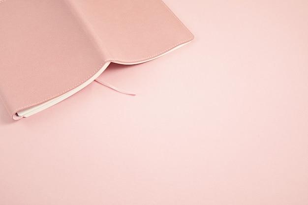 ピンクのパステルカラーの壁にノートブックを開きます。勉強、読書、リラックスのコンセプト。モノクロミニマルオプビュー