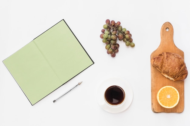 An open notebook; pen; grapes; coffee; croissant and halved orange on white background