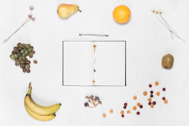 An open notebook and pen surrounded with different fruits over white backdrop