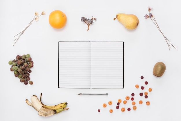 An open notebook and pen surrounded with ripe fruits over white backdrop