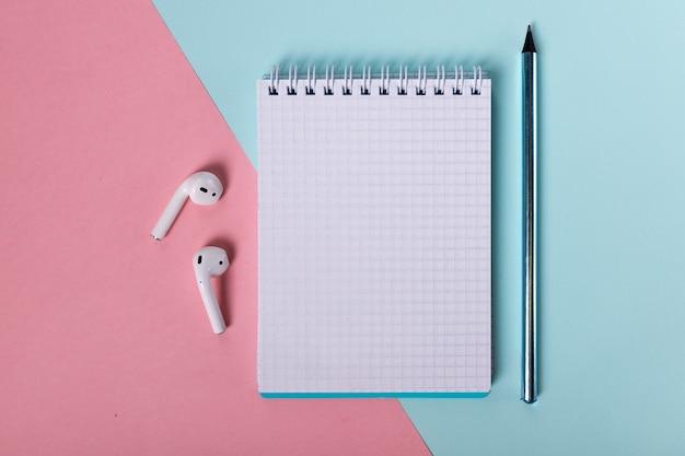 Открытый блокнот, карандаш и наушники красиво разложены на розово-голубом фоне вид сверху beaut ...