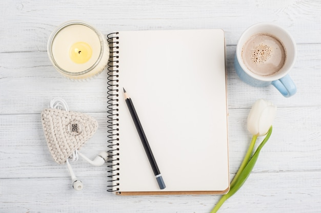 Open notebook, pencil, candle, earpods and tulip