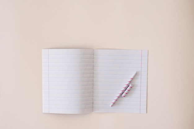 An open notebook in a ruler with clean sheets and a pen on a notebook on a kraft background. copy space