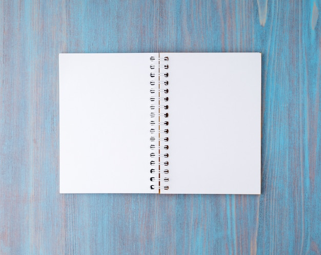 Open notebook on spring with white paper for notes and drawing. light background, blue woo