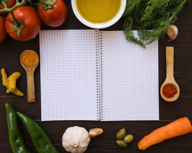 Open notebook surrounded by food ingredients.