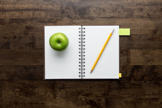 Open notebook with apple and pencil on wood table