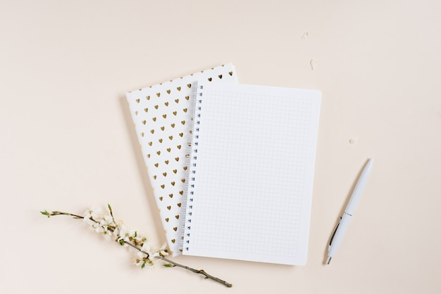 Open notebook with blank pages, pen, apple flower on beige background top view flat lay. fashion female blogger working desk. cotton flowers. lifestyle gentle background