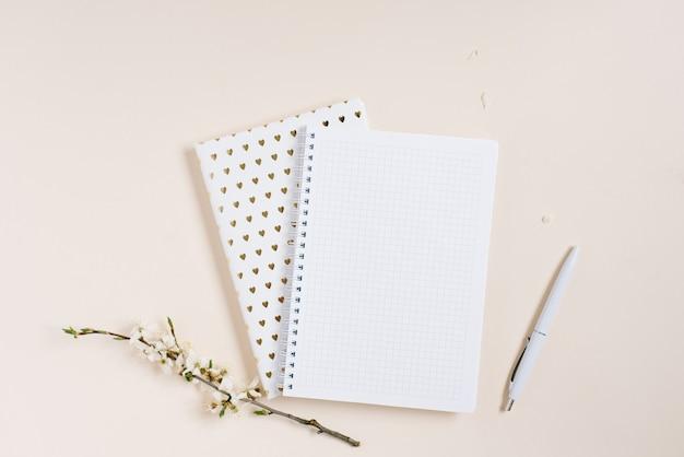 빈 페이지, 펜, 베이지색 배경 평면도에 사과 꽃이 있는 전자 필기장을 엽니다. 패션 여성 블로거 업무용 책상. 목화 꽃. 라이프 스타일 부드러운 배경