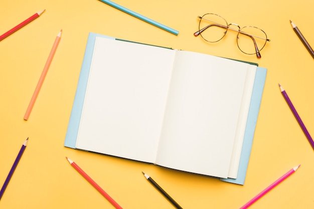 Open notebook with blank pages surrounded by pencils