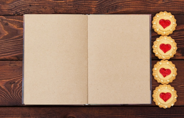 Open notebook with blank pages on wooden background, cookies in the shape of hearts