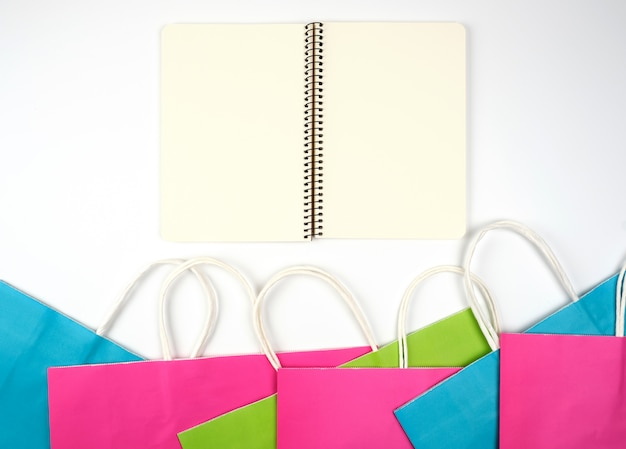 Open notebook with blank papersheets and multi-colored paper shopping bags