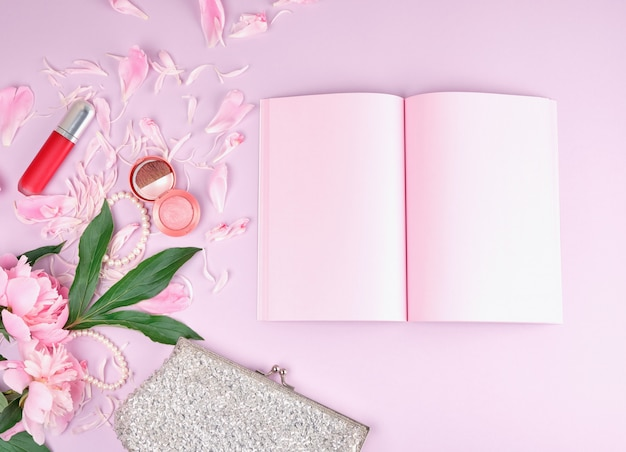 Open notebook with blank pink pages, bouquet of peonies