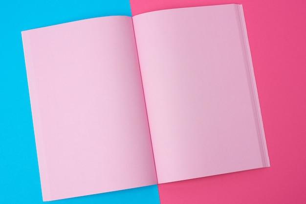 Открыть блокнот с пустыми розовыми страницами на синем фоне, вид сверху, плоская планировка