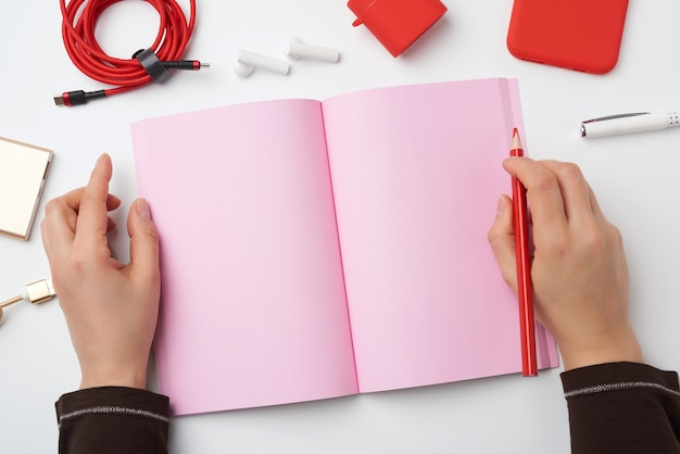 Open notebook with blank pink pages and two hands