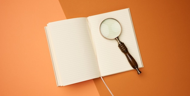 Open notebook with blank sheets and wooden magnifier on orange background, top view