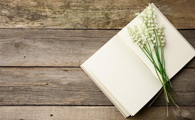 Открытый блокнот с чистыми белыми листами и букетом цветущих ландышей на деревянном столе из серых досок, вид сверху, копия пространства