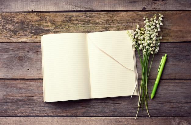 Открытый блокнот с чистыми белыми листами и букетом цветущих ландышей на деревянном столе из серых досок, вид сверху