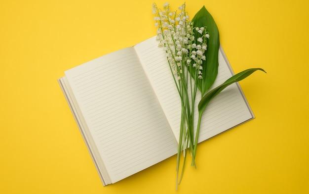 Открытый блокнот с чистыми белыми листами и букетом цветущих ландышей на желтой поверхности, вид сверху