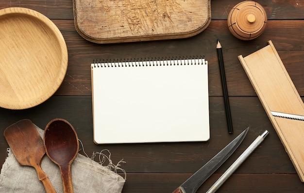 空白の白いシーツと台所用品でノートブックを開く