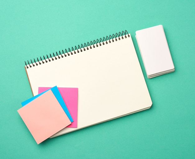Open notebook with blank white sheets, color stickers and rectangular business cards on a green background
