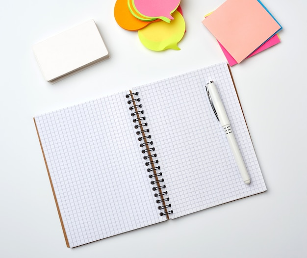 Open notebook with blank white sheets, color stickers and rectangular business cards