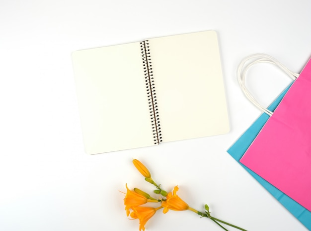 Open notebook with blank white sheets and multi-colored paper shopping bags