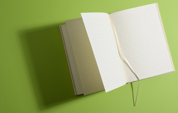 녹색 표면, 평면도에 빈 흰색 시트와 노트북을 엽니 다