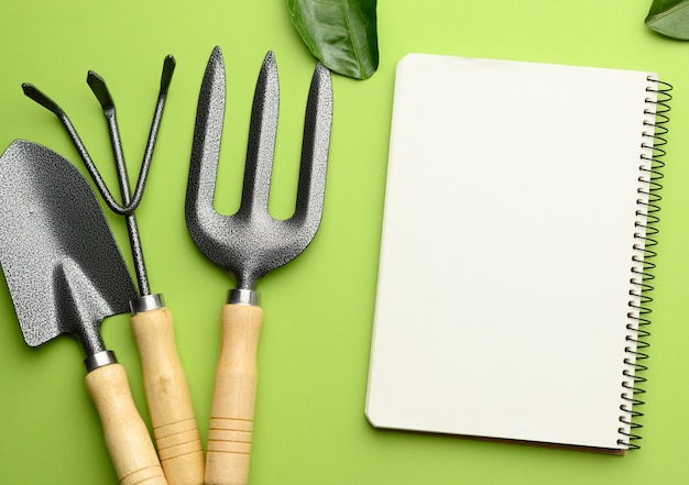Open notebook with blank white sheets and various gardening tools with wooden handles on green background, flat lay, copy space