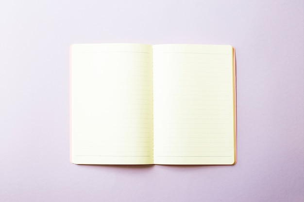 Open notebook with clean white sheets on a purple background