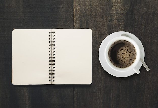Open notebook with cup of coffee on black wooden desk.