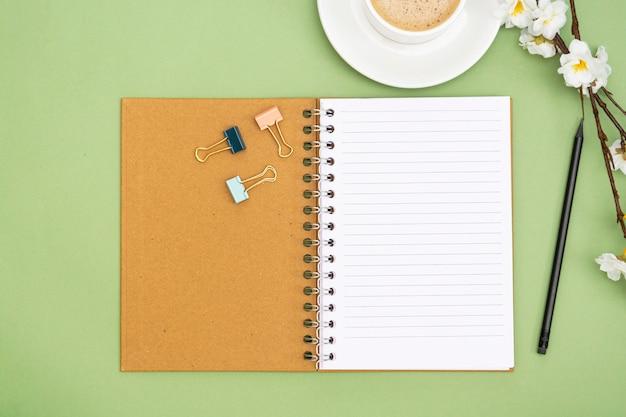 빈 페이지와 커피 컵 노트북을 엽니 다. 녹색 배경에 테이블 상단, 작업 공간입니다. 창의적 평신도.