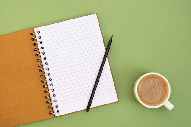 빈 페이지와 커피 컵 노트북을 엽니 다. 녹색 배경에 테이블 상단, 작업 공간입니다. 최소한의 평평한 평신도.