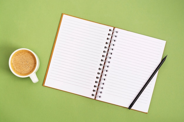 Open notebook with empty page and coffee cup. table top, work space on green background. creative flat lay.