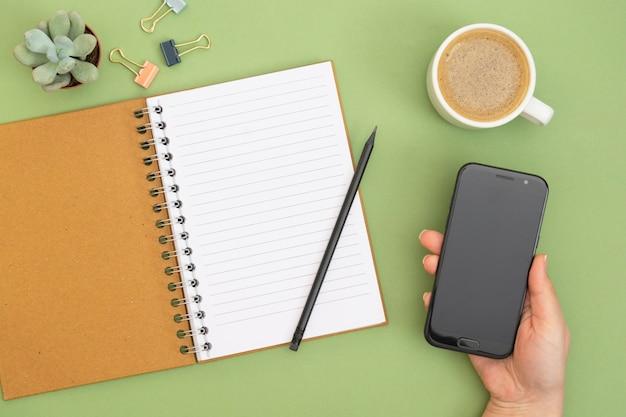 빈 페이지, 연필, 커피 컵과 손을 잡고 스마트 폰으로 노트북을 엽니 다. 녹색 배경에 테이블 상단, 작업 공간입니다. 창의적 평신도.