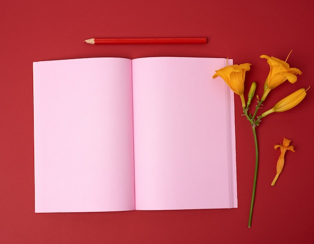 Open notebook with empty pink sheets and yellow flower