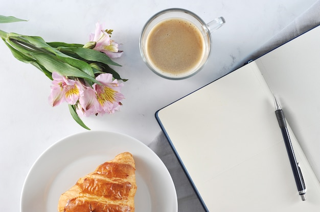 Open notebook with flowers and black coffee and croissant