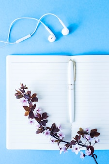Open notebook with headphones on a blue background