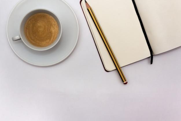 白い背景の上のペンとコーヒーカップでノートブックを開く作業コンセプトフラットレイコピースペース
