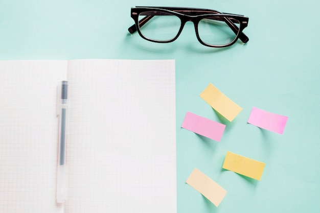 Open notebook with pen near adhesive notes and spectacles on colorful background