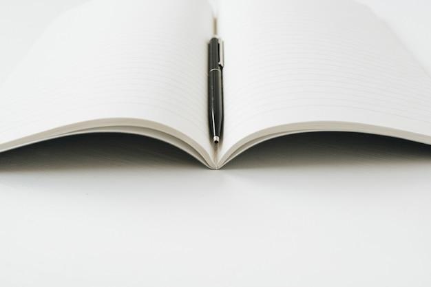白い表面にペンでノートブックを開く