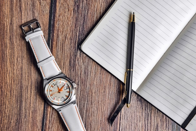 Open notebook with pen and wrist watch