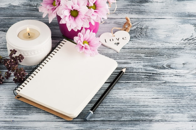 Open notebook with pink daisy flowers