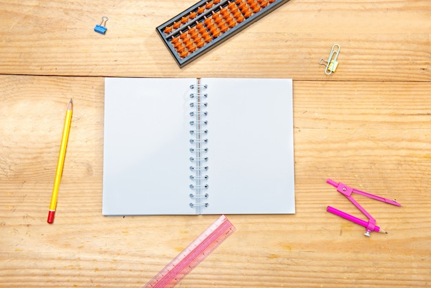 Open notebook with school supplies and stationery on the wooden table