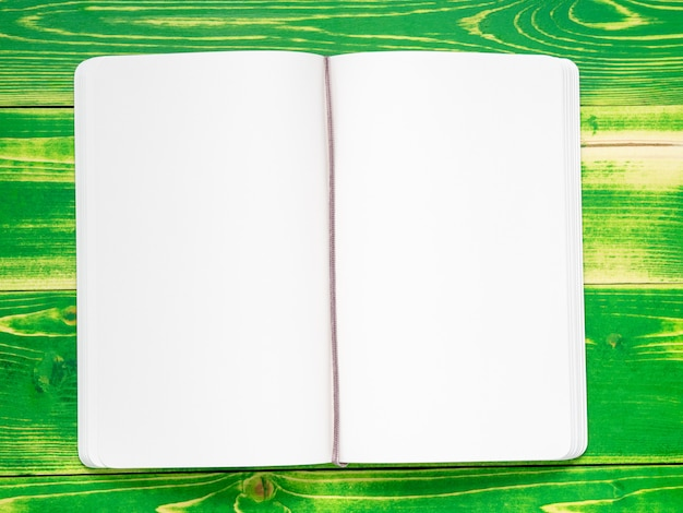 Open notebook with two, white pages, lying on a bright green wooden table, mock-up