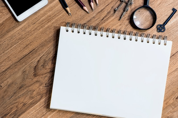 Open notebook with white blank sheets on wooden table
