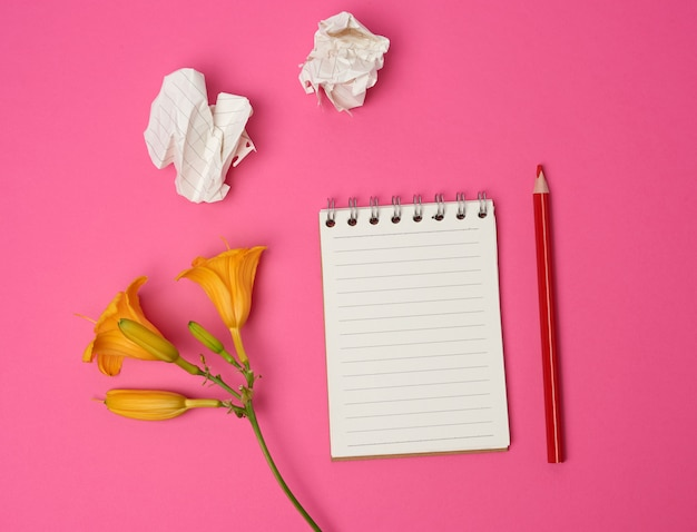 Open notebook with white sheets and yellow flower on a pink background