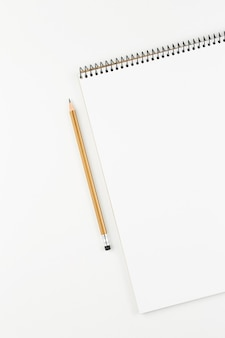 Open notebook with yellow pencil on white table top view, spiral notepad with blank page. flat lay of office concept, vertical view
