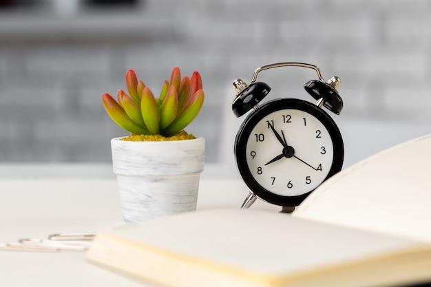 열린 메모장, 알람 시계 및 작업 테이블에 다즙